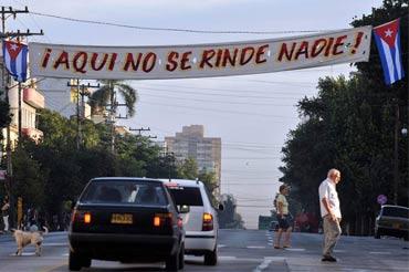 Varias personas caminan junto a un cartel de contenido revolucionario el sábado 24 de diciembre de 2011, en La Habana. EFE